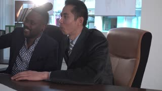 Pan on Asian and African American white collar workers working together at desk in office