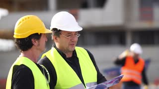 Senior civil engineer giving instructions to worker on construction site
