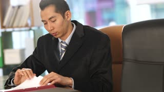 Thai financial manager analyzing documents sitting at his desk in office. Pan