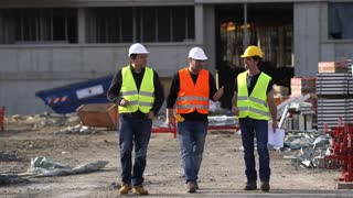 Three civil engineers at the end of their work shift on construction site