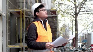 Worried and tired Asian apprentice engineer snorting on construction site