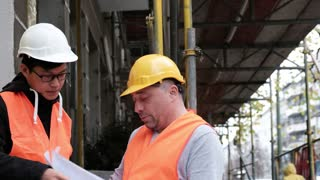Young Asian apprentice engineer at work on construction site with the senior manager. Outdoors