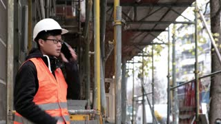 Young Asian engineer at work using his smartphone on construction site