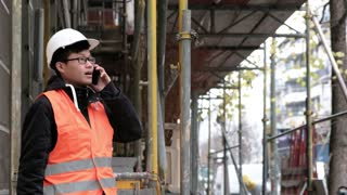 Young Asian engineer working using his smartphone on construction site