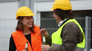 Work break at construction site: male and female engineers with safety jacket and yellow helmets drinking beer