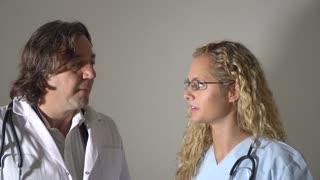 Worried doctor and nurse talking. Indoors