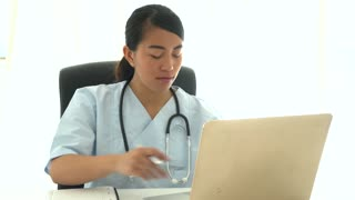 Young female asian doctor analyzing medical results at computer and taking notes