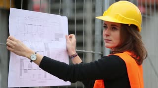Young female construction engineer holding office blueprints against scaffolding