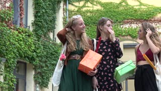 Young girls talking and laughing holding gift boxes