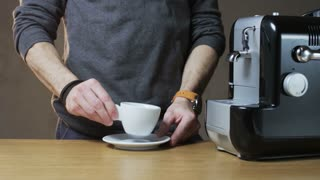 A Man Puts a Cup Into the Coffee Machine