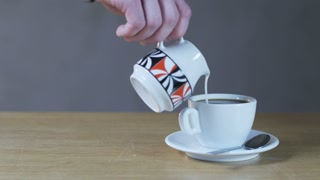 A Man Puts Little Cream Into a Coffee Cup