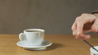 A man Puts Sugar Into a Coffee Cup
