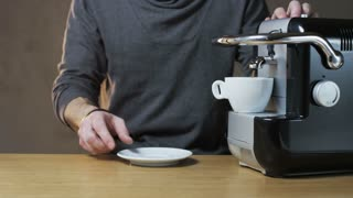 A Man Takes a Cup Out of The Coffee Machine