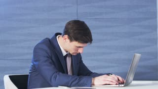 Businessman exhausted while working with a computer