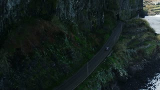 Car Going Near the Sea Along Mountain Slopes. Aerial Shot from Madeira