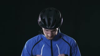 Cyclist putting on helmet. Healthy man wearing helmet and cycling glasses riding bicycle. Fitness workout  indoors on black background. Exercise in gym. Medium close up.