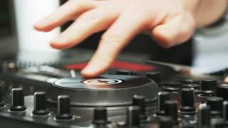 Disc Jockey Using DJ Mixer And Taking Headphones Off
