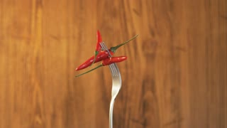 Fork With Three Chili Peppers on Wooden Background