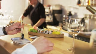 Man Eats Sushi Roll, Waitress Pours Wine