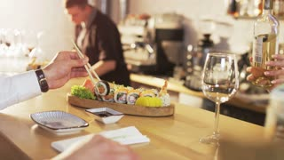 Man Holds Sushi Roll, Waitress Pours Wine