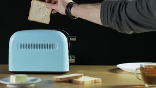 Man Puts Two Loaves of Bread Into an Electric Toaster