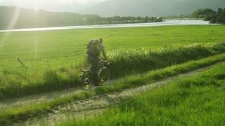 Man Riding a Bike Near the River. Drone shot