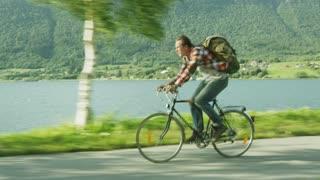 Man Riding Fast a Bike Near the River. Drone shot
