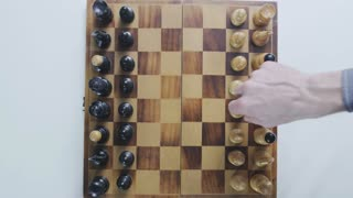 Plan view of a chess board. Beginning of the game. First moves. Static camera. White background.