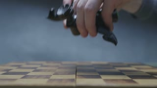 Player putting black chess pieces on chess board. Gradient gray background.