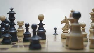 Playing chess. White horse beats black runner. Chess board rotation. Black pawn beats white horse. White background.