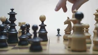 Playing chess. White horse beats black runner. Static camera. White background.