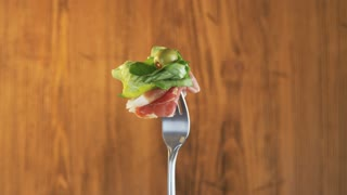 Rotating Fork With Ham and Lettuce on Wooden Background