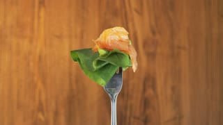 Rotating Fork With Salmon and Lettuce on Wooden Background