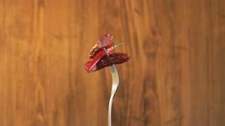 Rotating Fork With Two Sausages and Chili Pepper on Wooden Background