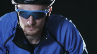 Sport cyclist in goggles and helmet and tight outfit 001. Healthy man wearing helmet and cycling glasses riding bicycle. Fitness workout  indoors on black background. Exercise in gym. Medium close up.