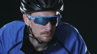 Sport cyclist in goggles and helmet and tight outfit 002. Healthy man wearing helmet and cycling glasses riding bicycle. Fitness workout  indoors on black background. Exercise in gym. Medium close up.