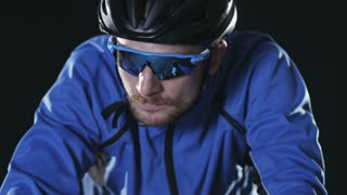Sport cyclist in goggles and helmet and tight outfit 003. Healthy man wearing helmet and cycling glasses riding bicycle. Fitness workout  indoors on black background. Exercise in gym. Medium close up.