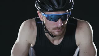 Sport cyclist in goggles and helmet and tight outfit 005. Healthy man wearing helmet and cycling glasses riding bicycle. Fitness workout  indoors on black background. Exercise in gym. Medium close up.
