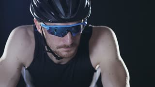 Sport cyclist in goggles and helmet and tight outfit 008. Healthy man wearing helmet and cycling glasses riding bicycle. Fitness workout  indoors on black background. Exercise in gym. Medium close up.