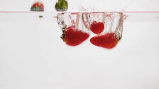 Strawberries falling into water in slow motion