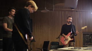 Two Men Playing Electric Guitars and a Vocalist Singing