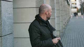 Bald Bearded Man Putting on a Winter Hat and Smoking