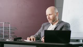 Bald Businessman Comparing Carefully Two Documents