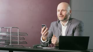 Bald Businessman Having a Successful Phone Call