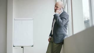 Bald Businessman Having an Important Phone Call