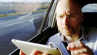 Bald Businessman in the Car Adjusting Headphones