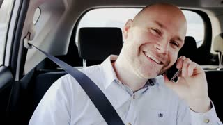 Bald Businessman in the Car Ending a Phone Call