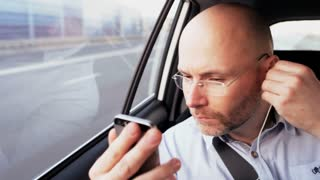 Bald Businessman in the Car Putting a Headphone On