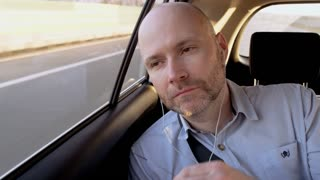 Bald Businessman in the Car Putting Glasses On