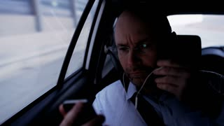 Bald Businessman in the Car Putting Headphone On